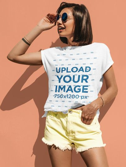 Placeit - T-Shirt Mockup of a Trendy Woman Posing by a Colored Wall