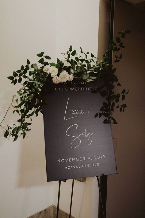 Lush smilax with a pop of white roses for a welcome sign at the Ultimate Skybox in Downtown San Diego by San Diego wedding florist, Le Champagne Projects #sandiegoweddingflorist #sandiegowedding #welcomesignflowers #weddingwelcomesign