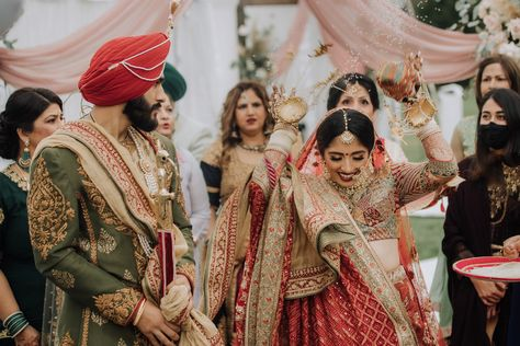 Indian bride throws rice at her wedding ceremony. Photograph by Catch Motion Photography, VA #wedding #photography #traditionalindianwedding #sikh #sikhbride #weddingphotography #covidwedding #backyardwedding #truelove