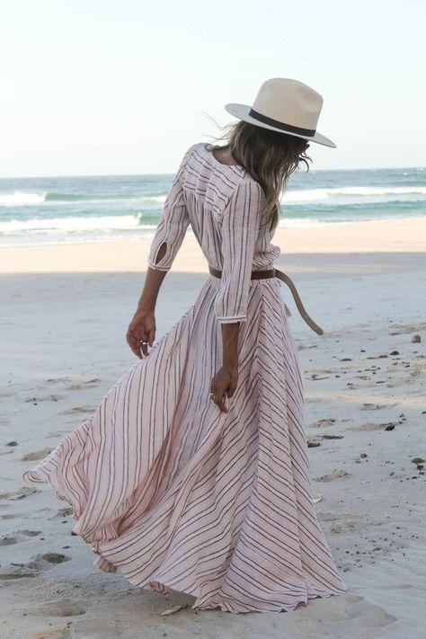 Au bord de la mer avec une robe longue d'été avec manches