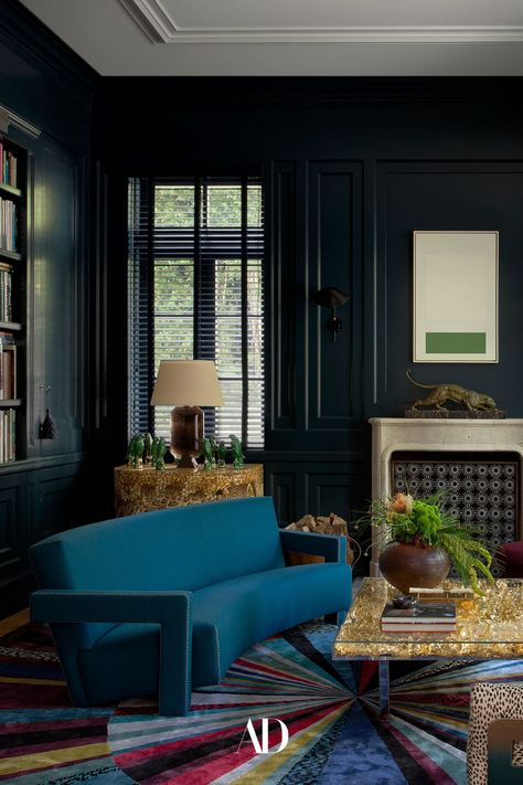 The library ensemble in the designer's home includes a Gerrit Rietveld sofa by Cassina, an Yves Klein table, a Marie Suri fire screen, a Piero Fornasetti cabinet, and a custom Tai Ping carpet by The Archers. The painting above the fireplace is by Karl Benjamin. The overall vibe of the space is much moodier than other rooms in the home with pops of color coming from the sofa and rug. #library #livingroom #familyroom #fireplace #coffeetable #bluepaint #lamp #den #office #homeoffice #wallart