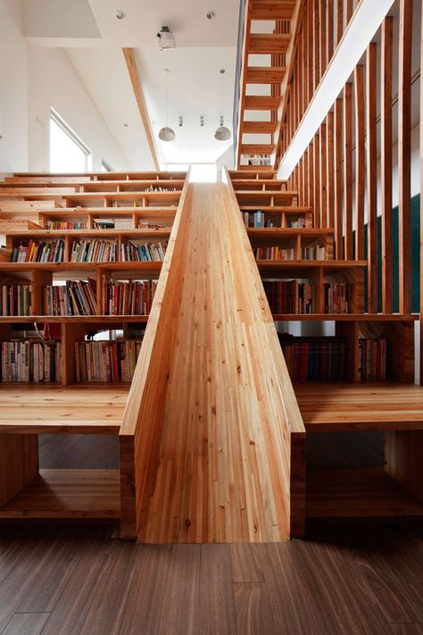 This Panorama House by the S.Korean architect Moon Hoon features a wooden slide built directly into a library which also functions as a stair-stepped home theater seating area. The clever design makes the library more creative and playful.