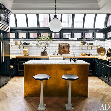 The kitchen is outfitted with cabinetry and butcher-block countertops by Fanuka; the island is clad in unlacquered brass and topped with Breccia Imperiale marble from Artistic Tile. The marble shelves rest on brackets from Liz's Antique Hardware; the subway tile is from Home Depot, the painting of Saint Peter is an 18th-century work from Peru, and the barstools are vintage American.