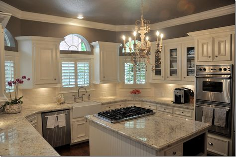 Light colored granite (Bianco Romano), cream colored subway tile, farm-style sink, Stardust by Benjamin Moore paint, and white cabinets.