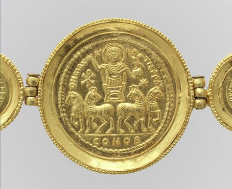 """On the back of the medallions the emperor is shown in military dress, standing in a chariot drawn by four horses. He holds a globe surmounted by a small Nike offering a crown of victory. To his side is a Christogram, symbolizing the religion of the Byzantine state."""