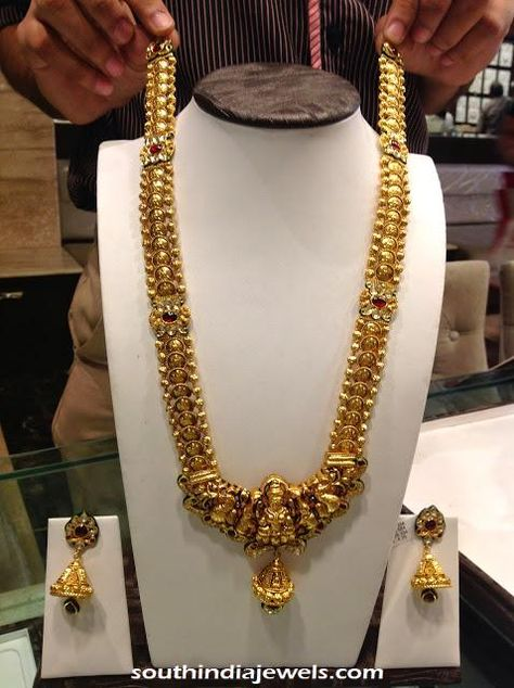 Gold Nakshi work temple jewellery long necklace with matching jhumkas.