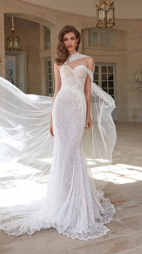 The soft mermaid #Simone Galia Lahav couture wedding dress is artfully draped with a delicate silk tulle and embroidered with scattered pearls and shimmery sequins features a sweetheart neckline, flowing skirt, and a sheer cape that attaches to the sweetheart neckline.