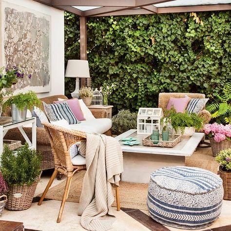 Terraza con muebles de exterior en fibras vegetales, pérgola, puff de tela, plantas y lámpara.