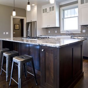 The crisp white Shaker-style cabinets contrast nicely with the dark wood island.