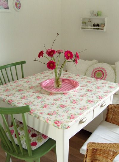 white table with floral oilcloth cover; pink and green with white background, pink tray, green chairs, granny square chair pads (!); quiet walls