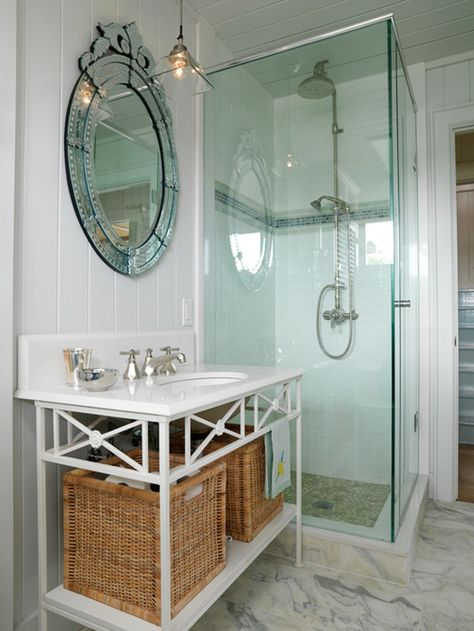 Designer Sarah Richardson placed two large wicker baskets on a vintage vanity shelf to keep bathroom toiletries at hand and to bring visual appeal to the all-white bathroom. The vanity's vintage design provides a place to hang towels.
