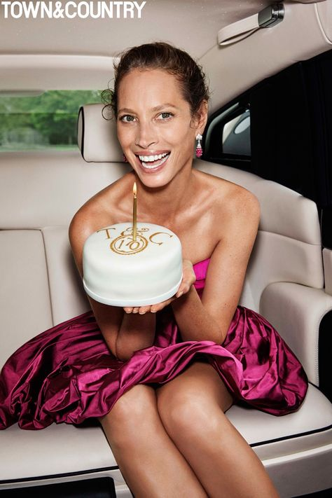 Posing with a cake, model Christy Turlington wears a pink Oscar de la Renta…