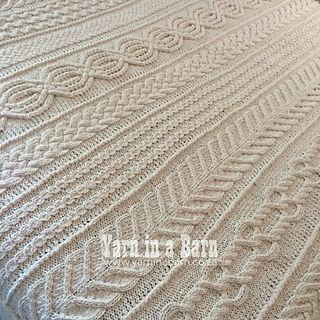 The Aran Caresse Cable Afghan is a modular design, knitted in separate strips, which are then joined together in such a way that the join resembles another cable.
