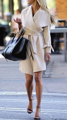 Rich Look With Splendid Winter Outfits Woman in white trench coat carrying black leather handbag walking through gray asphalt road.