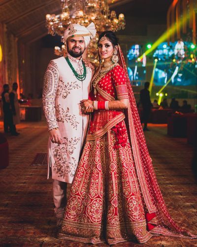 Contrasting Bride And Groom Outfits In Red And White Couple Wedding Dress Indian Wedding Outfits Wedding Outfits For Groom