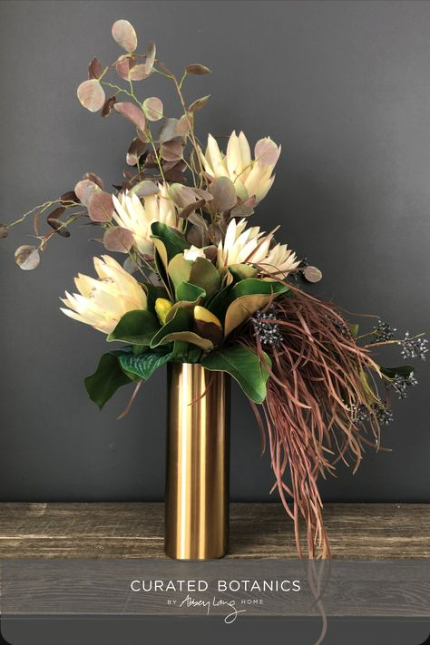 This moody, elegant display is modern with a rustic touch. The brass vase is a stunning piece in its own right and works so well with the subtle colourings of the proteas, magnolia, viburnum berries, eucalyptus and hanging foliage. #curatedbotanics #fauxflowers #brassvase #proteas #flowerarrangement