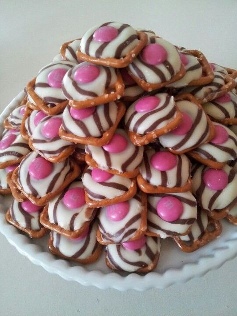 Pretzel Hugs with pink MM's! The perfect Pink Zebra Party snack! ;)  All you need is a square pretzel, a Hershey Hug, and a M and M. Bake in the oven at 200°F for 3-4 minutes. by virginia