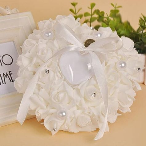 Store the most precious tokens of the bride and groom's special day in this luxe faux rose ring bearer pillow! This heart-shaped rose pillow has the perfect niche for two rings to be safely stored and delivered to the alter in elegant style. The rose heart looks great in pictures both down the aisle and with ring photos, and is sure to impress all guests lucky enough to be in attendance! Features: Material: Ribbons, Faux Pearls, Rose Flowers, Rhinestones Size: Approx. 6.3 x 2.75 x 2.75 inches Pa