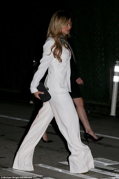 Dance fever! She strutted into the hotspot wearing a fashionable flared white suit, which showed off her cleavage