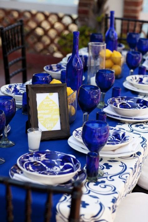 Blue and white table setting ideas via Style Me Pretty. I love cobalt blue glassware, and look how fun the setting is with the brilliant color overflowing. The cobalt blue bottles fit right in.