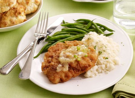 """Tyler Florence's Chicken Fried Steak: """"My first memory of eating this dish was in Georgia when I was 7 and I joined my grandmother """" Florence Mama"""" in the kitchen. Wrist deep in buttermilk and flour, I stood and helped as she pan-fried steaks in bacon drippings in her 100-year-old cast-iron skillet. Then, with the back-door screen letting in a warm breeze scented with sweet Georgia pine, I tasted it—the perfect bite. The crunchy, fried, flour-coated pieces of beef, smothered in a creamy milk gravy with lots of black pepper, ignited a passion for cooking that still crackles. """""""
