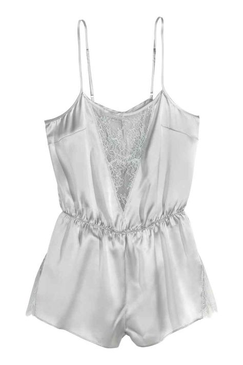Jumpsuit in satin made from mulberry silk with lace inserts. Narrow, adjustable shoulder straps, opening at back with covered button, elasticized seam at waist, and short legs.