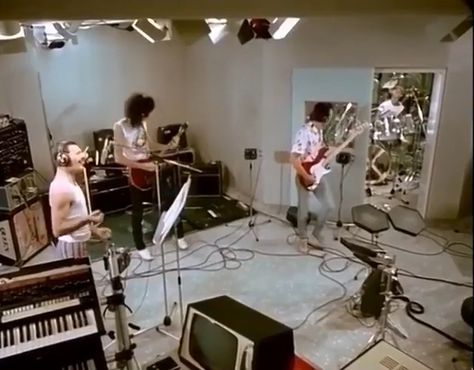 Freddie Mercury, Brian May, Roger Taylor, and John Deacon messing around in the studio.
