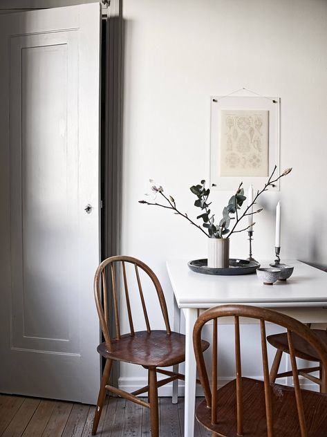 Calm and peaceful dining spot with white table and old wooden chairs in white dining room