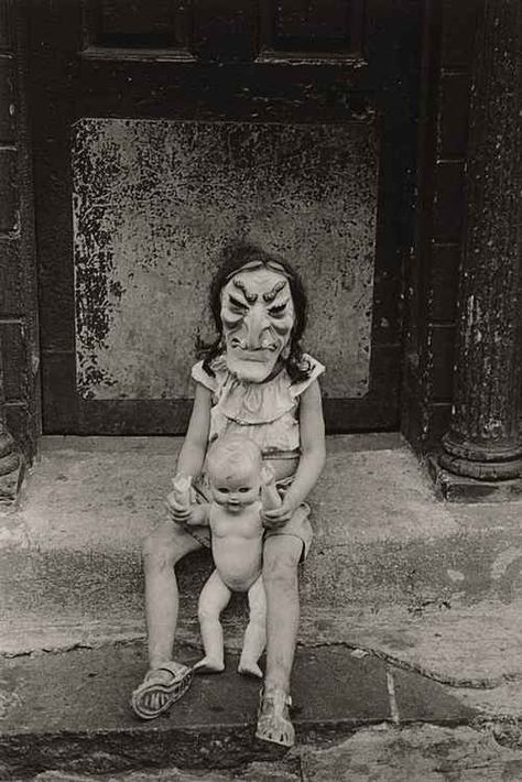 Masked Child with a Doll, 1961 photo byDiane Arbus