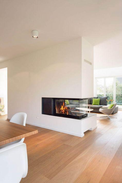 Der 3-seitige Kamin ist als Raumteiler zwischen Bestandsgebaede und Neubau konzipiert. Er trennt das Esszimmer vom Wohnbereich. Sockelabdeckung und Regla auf der rechten Seite sind aus Rohstahl gefertigt.