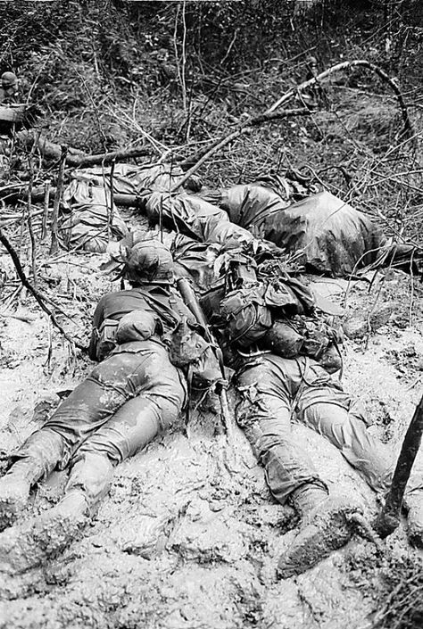 Two infantrymen, half submerged in slimy, stinking mud, crawl forward near three dead soldiers wrapped in ponchos in War Zone D, Vietnam, 1967. They fought in dense jungle between muddy bomb craters. #VietnamWarMemories