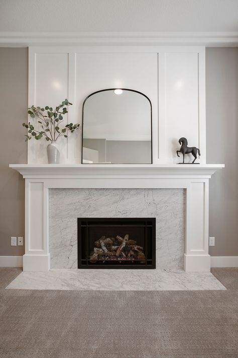 Honed Carrara marble slab used as a fireplace surround with white recessed panels and mantle. Fireplace Feature Wall, Marble Fireplace Surround, Brick Fireplace Makeover, Bedroom Fireplace, Fireplace Design, Marble Fireplaces, Living Room With Fireplace, Fireplace Surrounds, Home Living Room