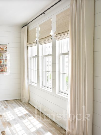 stock image of a row of three windows on a white wall with ivory drapes and shades and sunlight streaming into the room love love love pinterest