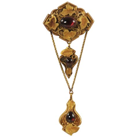 "Art Nouveau 14k gold and cabochon garnet brooch/pendant with This fascinating piece of jewelry comes apart so it can be worn many ways. There is a bale so it can be worn as a pendant and the pin back has a ""hood"" on it so it wont stick you when wearing as a pendant. Each of the two smaller gold and garnet pieces come off and can be worn as pendants. The large piece can be worn as a pendant or brooch. Even the two gold chains are removable. The leaves on the piece are done with great detail."