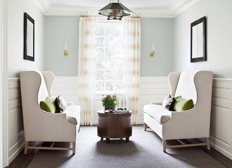 """This cozy seating area boasts gray blue paint (""""Benjamin Moore HC-147 Woodlawn Blue"""" ) on upper walls and stacked wainscoting on lower walls."""