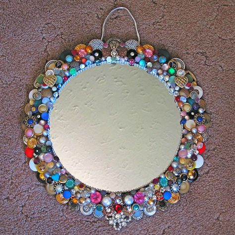 Mosaic like using buttons surrounding mirror.  Beautiful design.