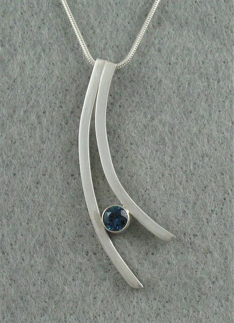 Pendant: sterling silver, tube set London blue topaz. Handmade by Jeanne Boydston. The inspirations for my jewelry come from my own life experiences, observations and imagination. The seed for a new jewelry design may come from an organic form in nature or something as mundane as a light fixture.