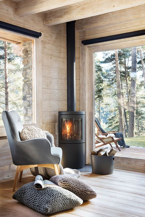 Contemporary Cabin Space With Home Wood Burning Stove A contemporary cabin space with large windows, wood clad space and a modern wood burning stove in the corner.