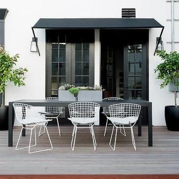 Long Black Outdoor Dining Table With White Bertoia Chairs Outdoor Tables And Chairs White Outdoor Table Outdoor Furniture Ideas Backyards
