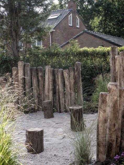Robinia palen met een vuurplaats en boomstammen als krukjes in een natuurlijke tuin aan de duinen. Ontwerp en realisatie door De Peppels Tuinen