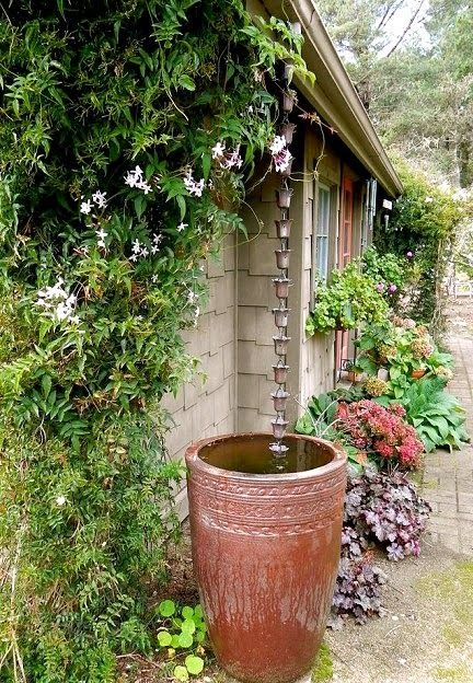 Rain chain into a rain barrel. So much prettier than a gutter/downspout. I already have the rain chain ~R