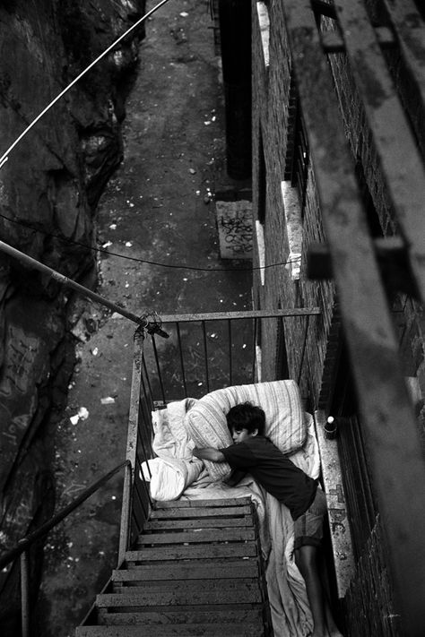 Ten-year-old boy sleeps on the fire escape, where he slept all night. Homeless, kid, child, stairs, powerty, alone, sad, powerful image, intense, strong, photo b/w.