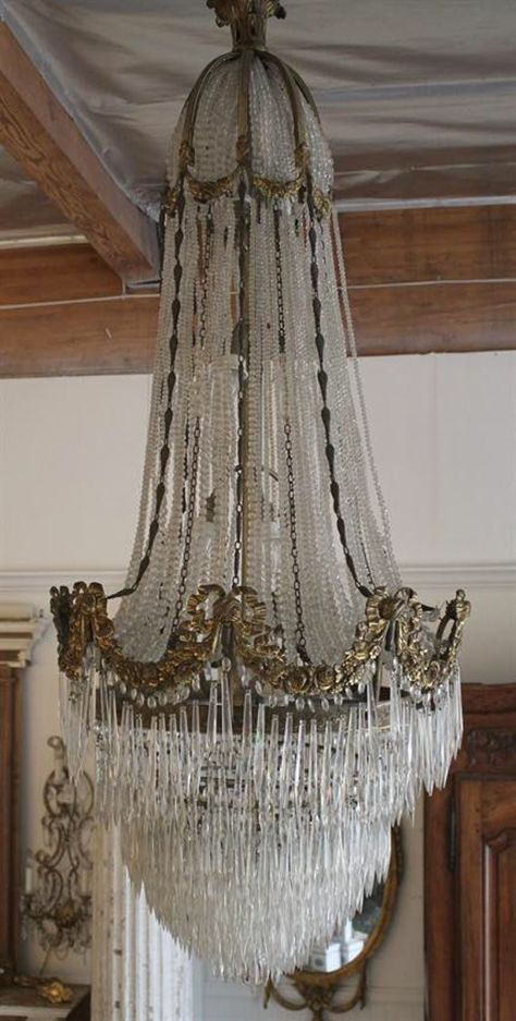 Exquisite gilt bronze chandelier, with rose swags and hundreds of crystal spears. English cut beaded strands hang like jewelry. This chandelier just sparkles at all angles, the frame does have a wonderful aged patina. The bottom can be removed for shipping, and does appear to have a few of the
