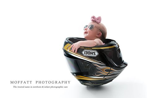 Newborn baby girl with aviator sunglasses in a black motorcycle helmet.