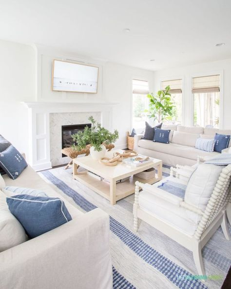 Gorgeous coastal inspired living room area with a blue and white stripe rug, white Pottery Barn sofa, neutral decor, summer decor, and throw pillows.
