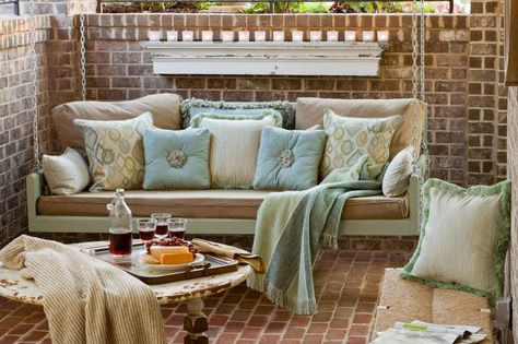 This cottage-style brick patio features a cozy porch swing with weather-resistant pillows and throw. A wood bench and small round table fill out this outdoor space.