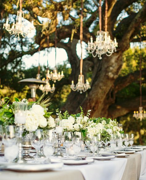 silver accents, chandeliers, and lush whites with leaves, silver chargers