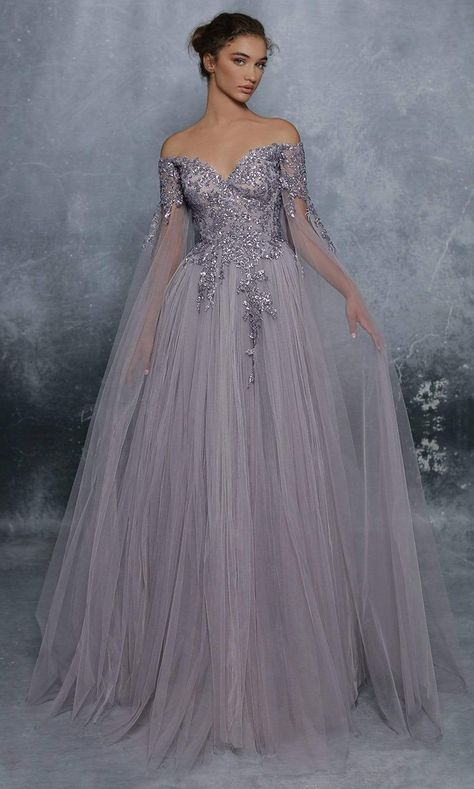 Radiate an aura of pure sophistication in this luxuriously made Tarik Ediz 96075 Evening Gown. Designed in richly gathered tulle forming an A-Line silhouette, this ensemble shows a sweetheart off-shoulder neckline flanked with long sheer draping cape sleeves, with glimmering embroidery appliques adorning the fitted bodice while the back shows off a V-shape with the zipper closure at the center. The gathered skirt gracefully completes a full-length hemline and a train. Elevate your status into th Tulle Gown, Ball Gown Dresses, Pageant Dresses, Formal Dresses, Long Ball Dresses, Reign Dresses, Sheer Gown, Blue Ball Gowns, Long Gowns