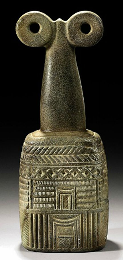 """Mesopotamian Stone Spectacle Idol, c. 3000 BCE. The architectonic base of rectangular form with rounded edges, decorated with reed houses with characteristic arching doorways, band of zigzags and chevrons above, the """"eyes"""" on a long conical-shaped neck."""