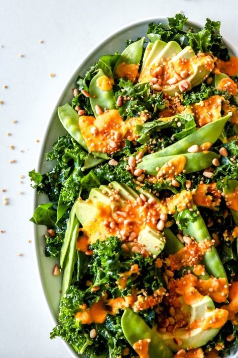 Kale Avocado Crunch Salad is loaded with healthy ingredients and topped with a deliciously sweet Ginger Carrot Dressing. thetoastedpinenut.ccom #thetoastedpinenut #kalesalad #carrotgingerdressing #kaleavocadosalad